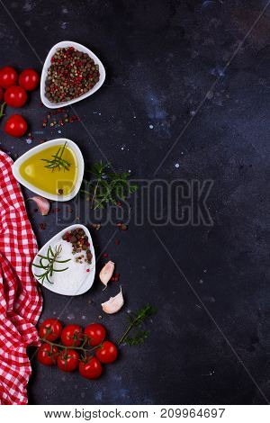Food background - spices, olive oil and tomatoes on black background