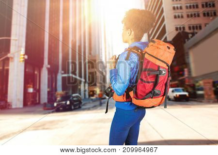 Full length of hiker standing with camera and backpack against new york street
