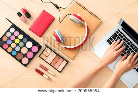 Hands of beauty blogger with laptop and different stuff on table