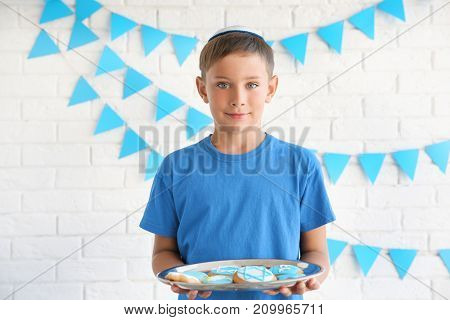 Jewish boy holding tray with festive Hanukkah cookies at home