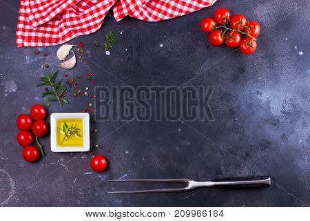 Food background - spices, olive oil, meat fork and tomatoes on black background