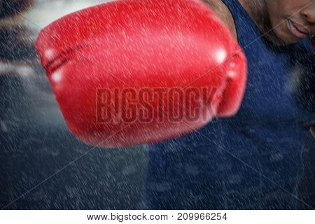 Fit man boxing with gloves  against forked lightning against sky