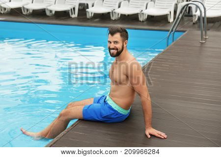 Handsome young man relaxing near blue swimming pool