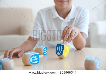 Jewish boy playing with dreidel at home