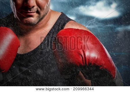 Boxer performing boxing stance against road against overcast sky with lightning