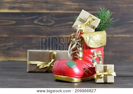 Christmas boot and gifts on wooden background