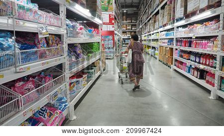 Grandma (my mother) looking the washing powder and pushing a shopping cart at Makro Sainoy branch Bangbuathong provice Thailand Asia 17 October 2017 01:00 PM.