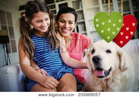 Cute heart decorations against mother and daughter sitting with dog in living room