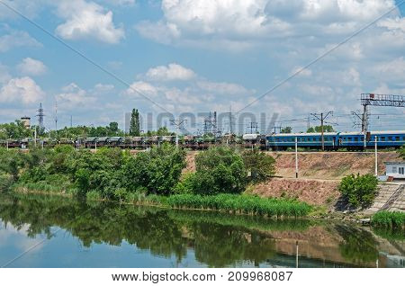 Military train echelon is moves towards the bridge across river against background of the cloudy sky