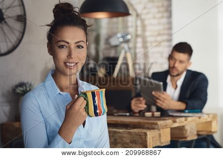 Attractive young businesswoman drinking tea, smiling happy.