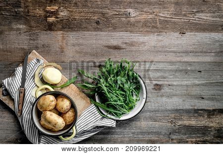 Young potatoes and fresh arugula sitting on wooden table, topview, additional textspace left on side