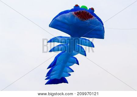 Blue kite that is flying. Blue fish kite.