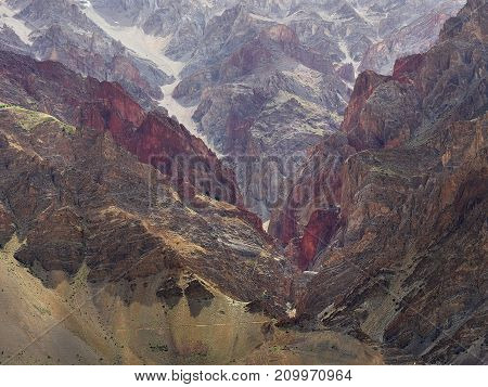 The mountains are many colors: red burgundy brown yellow are like stone waves modern interior photography Tibet.