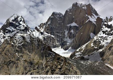 Steep peaks high mountains glacier: eternal snow-white ice and steep cliffs under the gloomy sky in the clouds the Himalayas.