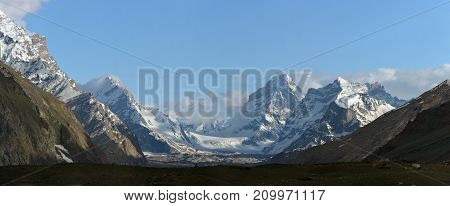 High mountains glacial valley: peaks covered with eternal ice moraine descends to the river clouds lie among the mountains blue sky Tibet.