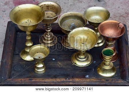 Buddhist oil lamps on high legs stand on a dark old wooden tray preparing for an evening service in Tibet monastery.