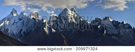 High mountains range of the central Himalayas: the sharp peaks of the peaks are covered with perpetual glaciers the blue sky with a white cloud Northern India.