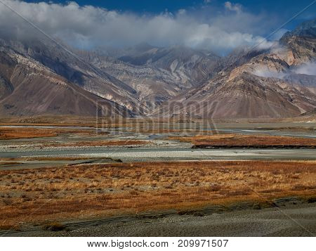 Autumn in the high mountains: clouds ridge to the tops of colored peaks the blue river flows through the valley among the orange vegetation of the shores.