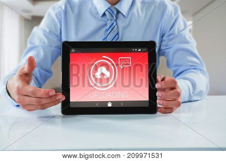 Businessman showing digital tablet against uploading text with icon screen