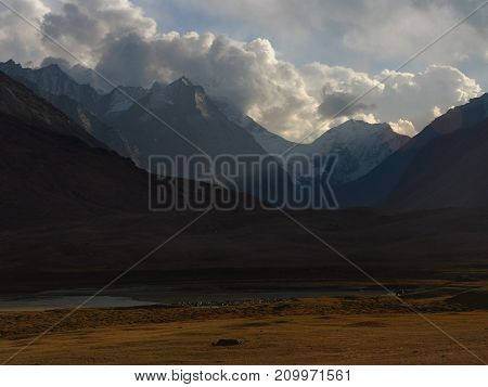 Sunset in the high mountains: the last rays of the sun illuminate the snowy peaks huge cumulus clouds on the blue sky foreground the yellow field autumn in the Himalayas.