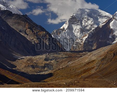 Autumn in the high mountains: the slopes of the mountain and moraine are covered with a carpet of yellow vegetation over the snowy peak of the peak curl clouds Tibet the Himalayas.