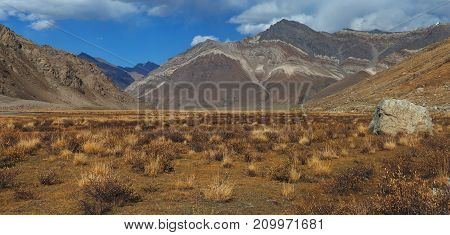 Orange mountain valley autumn in the Himalayas: red mountains foul vegetation white clouds in the blue sky.