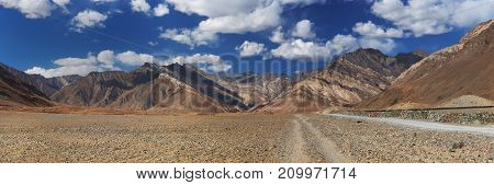 Country mountain road: the track stretches along the high mountains of the desert among the colored brown mountains with folds of rocks autumn in the Himalayas.