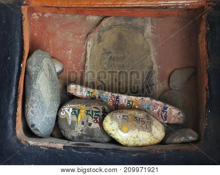 The niche in the burgundy wall of the Buddhist monastery where huge stones with colored inscriptions in Sanskrit are located prayer mantras the Himalayas Tibet.