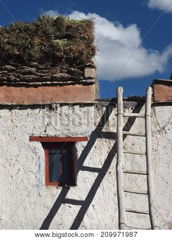 Tibetan house: a white wall a small window a ladder on a flat roof lay the stocks of brushwood for winter Tibet.