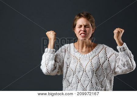 A dark haired pretty girl with short hair on a black background holds her hands raised folded into a fist. Close-up. Anger.