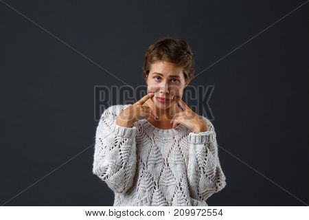 Dark-haired beautiful girl with short hair on a black background pulls a smile with her index fingers. Emotion is sad. Close-up.