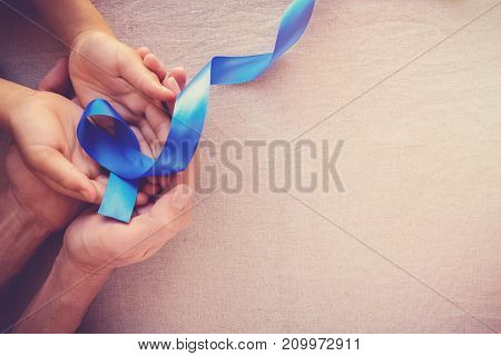 adult and child hands holding Blue ribbon Colon Cancer Colorectal Cancer Child Abuse awareness world diabetes day