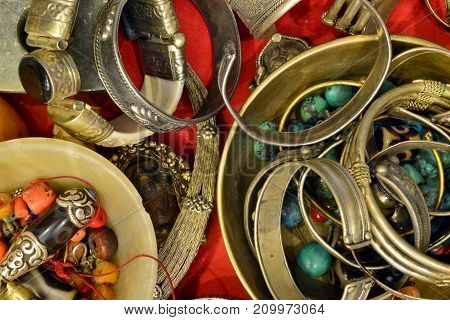 Many ancient Buddhist bracelets lie in the shop window among the red coral beads and blue turquoise modern interiors photo design.