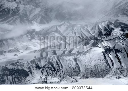 High chains of the Himalayas in winter: peaks and slopes are covered with snow around white clouds black and white photography.