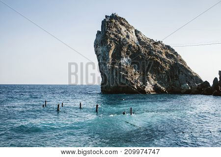 Rock in the sea and the ruins of the pier. Russia, the Crimea.