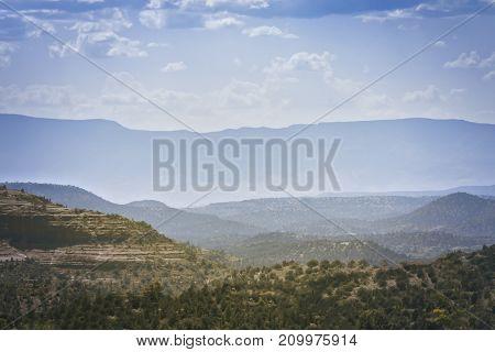Foggy mountain ridge with cloudy blue skies
