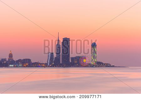 View from Sea Beach to Illuminated cityscape with Skyscrapers And Tower at sunset, Batumi, Adjara, Georgia