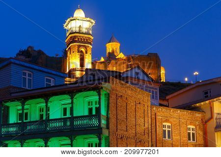 Amazing View of Jumah Mosque, Sulphur Baths and famous colorful balconies in old historic district Abanotubani in night Illumination during morning blue hour, Tbilisi, Georgia.