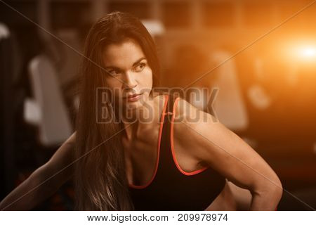 Sporty girl in gym doing exercises. Portrait of fitness woman.