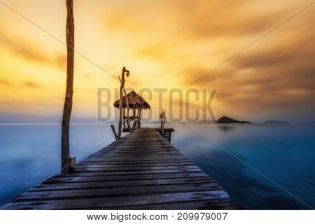 abstract sunset on seascape with wood sea dock on smooth orange and blue color - can use to display or montage on product