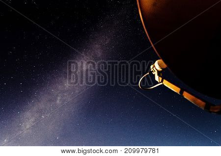 Side View Orange Satellite Dish TV Antenna at night with a milkyway background with grain
