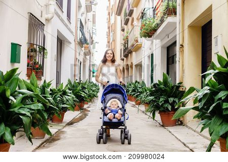 Mother walking with a baby pram (stroller, carriage) in town. Love and family concept.
