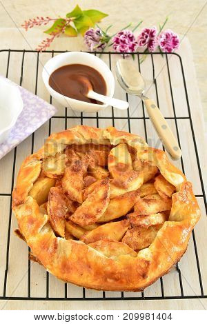 Fresh baked apple galette in puff pastry with salted caramel sauce. Vertical format and shot in natural light.
