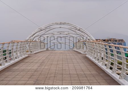 White metal crossbeam foot bridge with metal railings on gray misty morning