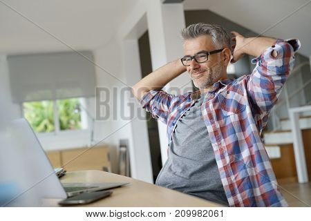 Home-office worker stretching arms in front of laptop