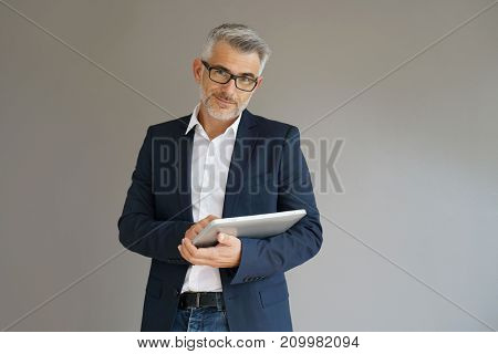 Trendy businessman using tablet, isolated