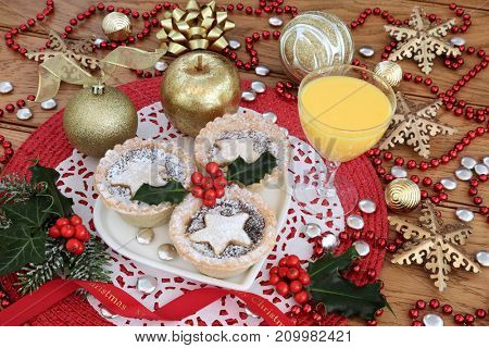 Mince pies with holly on a heart shaped plate with eggnog drink, gold  bauble decorations and bead strand on red place mat on oak wood table background.