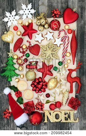 Symbols of christmas background with bauble decorations, noel sign, mince pies, gingerbread cookies and foil wrapped chocolates on parchment paper and rustic wood.