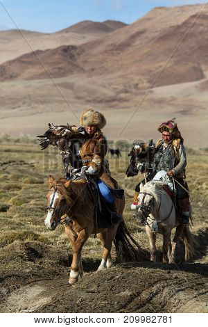 SAGSAY, MONGOLIA - SEP 28, 2017: Kazakh Eagle Hunters traditional clothing, while hunting to the hare holding a golden eagles on his arms in desert mountain of Western Mongolia.