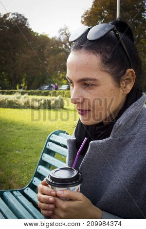 Girl with a cup of coffee in the park
